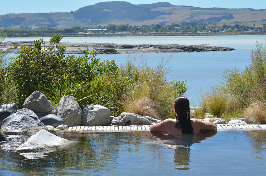37197946 - young woman having a spa in outdoors hot pool in rotorua, new zealand.